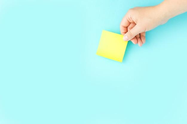 Ręka trzyma żółtą naklejkę. pisanie notatek, codziennych planów i przypomnień