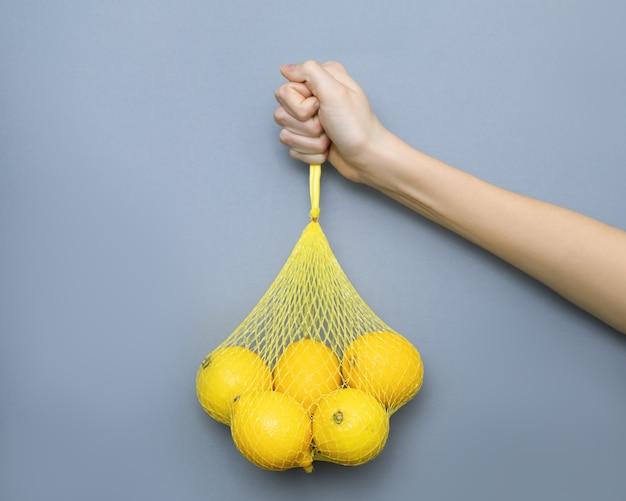 Ręka trzyma żółtą siatkę z cytrynami