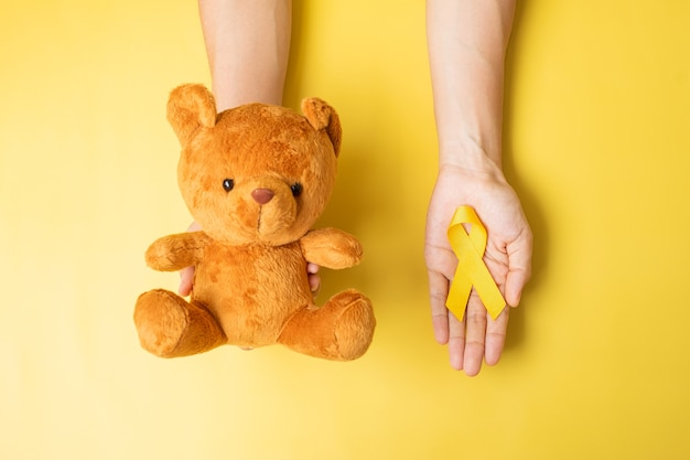Ręka trzyma żółtą wstążkę i lalkę miś na żółtym tle do wspierania życia i choroby dziecka. miesiąc świadomości raka u dzieci we wrześniu i koncepcja światowego dnia walki z rakiem