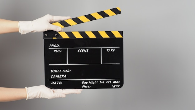 Ręka trzyma żółty i czarny clapper board kolor lub film clapperboard i nosi białą rękawiczkę medyczną na szarym tle.