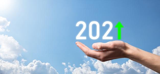 Ręka trzymać 2021 pozytywną ikonę na tle nieba. plan biznesowy pozytywny wzrost w koncepcji roku 2021. biznesmen plan i wzrost pozytywnych wskaźników w jego działalności, dorastanie koncepcji biznesowych.