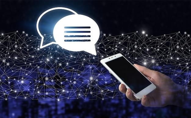 Ręka trzymać biały smartphone z cyfrowym hologramem znak e-mail i sms na ciemnym tle niewyraźne miasta. koncepcja biznesowa e-mail. marketing symbol lub biuletyn. centrum wsparcia technicznego obsługa klienta.