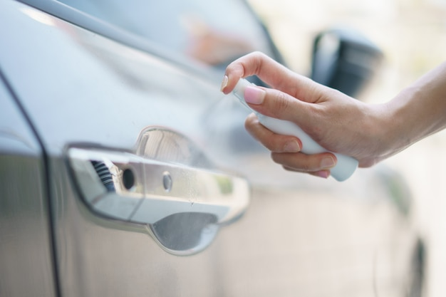 Ręka trzymać butelkę rozpylanie alkoholu dezynfekcja klamki drzwi samochodu, ochrona przed wirusami.