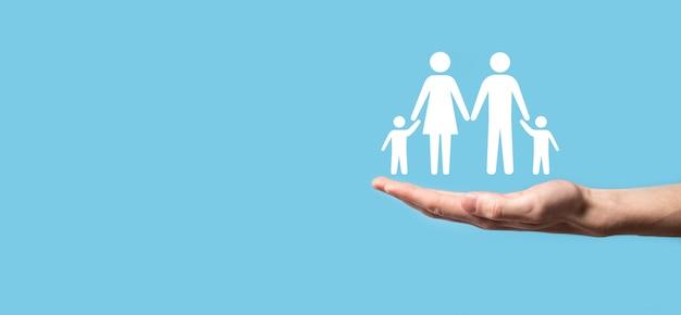 Ręka trzymać ikonę młodej rodziny. rodzinne ubezpieczenie na życie, wsparcie i usługi, polityka rodzinna i wspieranie koncepcji rodzin. koncepcja szczęśliwej rodziny. miejsce na kopię. rozłożone ręce przedstawiające papierową rodzinę człowieka