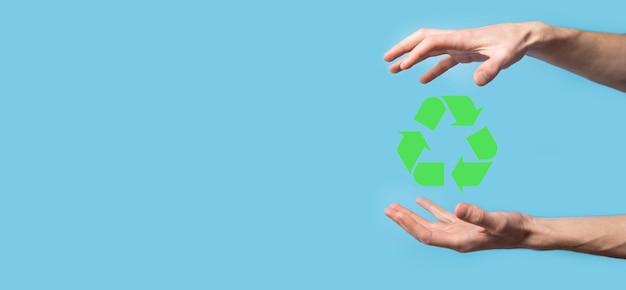 Ręka trzymać ikonę recyklingu. koncepcja ekologii i energii odnawialnej. znak eco, koncepcja zapisz zieloną planetę. symbol ochrony środowiska. recykling odpadów. symbol dnia ziemi, pojęcie ochrony przyrody.