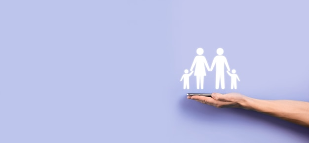Ręka trzymać młoda rodzina ikona. rodzinne ubezpieczenie na życie, wsparcie i usługi, polityka rodzinna i wspieranie koncepcji rodzin. koncepcja szczęśliwej rodziny. kopiuj space.mancupped ręce przedstawiające rodzinę mężczyzny.