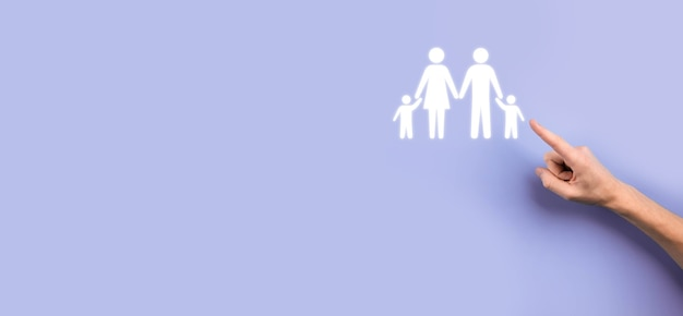 Ręka trzymać młoda rodzina ikona. rodzinne ubezpieczenie na życie, wsparcie i usługi, polityka rodzinna i wspieranie koncepcji rodzin. koncepcja szczęśliwej rodziny. skopiuj przestrzeń. mancupped ręce pokazujące papierową rodzinę