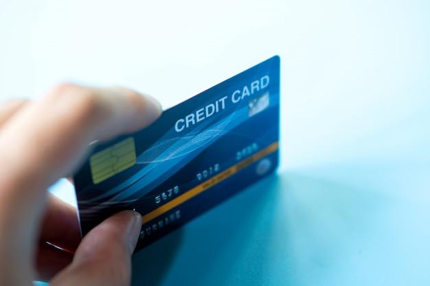 Ręka trzymać niebieskie tło karty kredytowej firmy