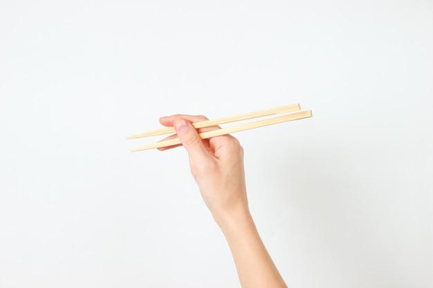 Ręka trzymać pałeczki na biały. minimalistyczna koncepcja żywności. widok z góry
