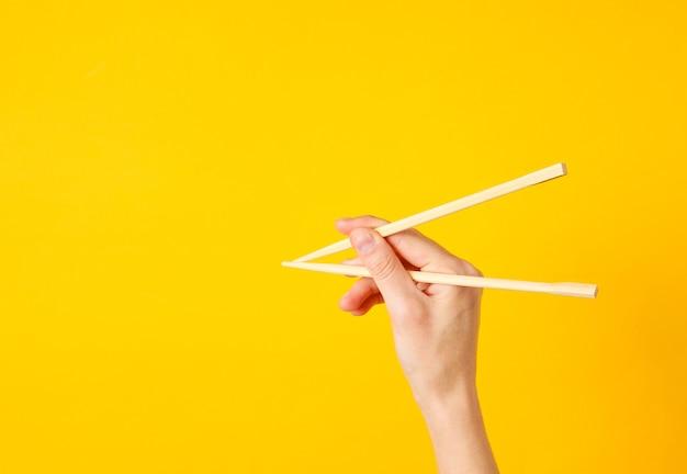 Ręka trzymać pałeczki na żółto. minimalistyczna koncepcja żywności. widok z góry
