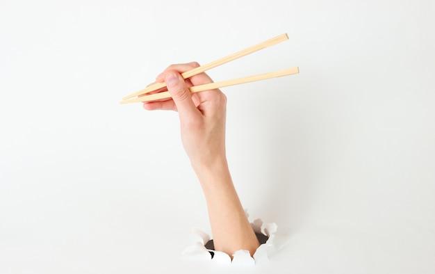 Ręka trzymać pałeczki przez rozdarty otwór na białym tle. minimalistyczna koncepcja żywności. widok z góry