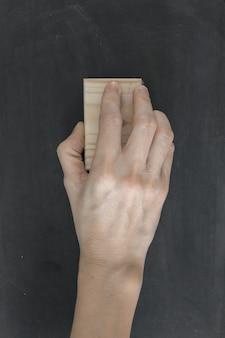 Ręka trzymać pędzel usunąć na tablicy.