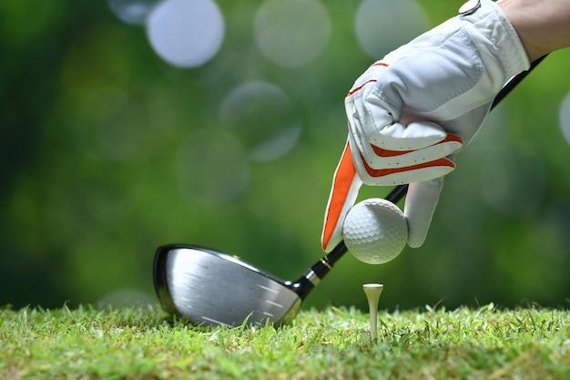 Ręka trzymać piłkę golfową z tee na polu golfowym