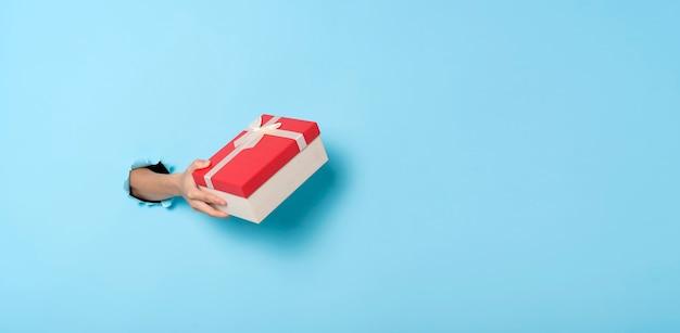 Ręka trzymać pudełko z dziury w ścianie na niebieskim tle.