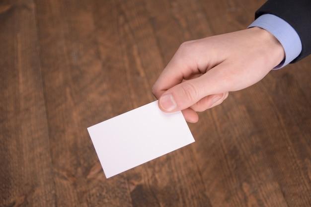 Ręka trzymać pustą białą kartę makiety