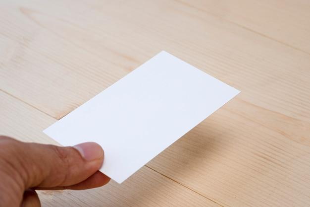 Ręka trzymać pustą białą wizytówkę