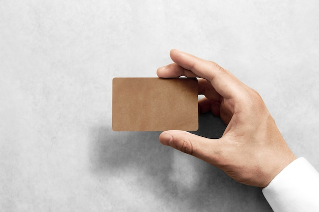 Ręka trzymać pustą kartę rzemiosła z zaokrąglonymi narożnikami