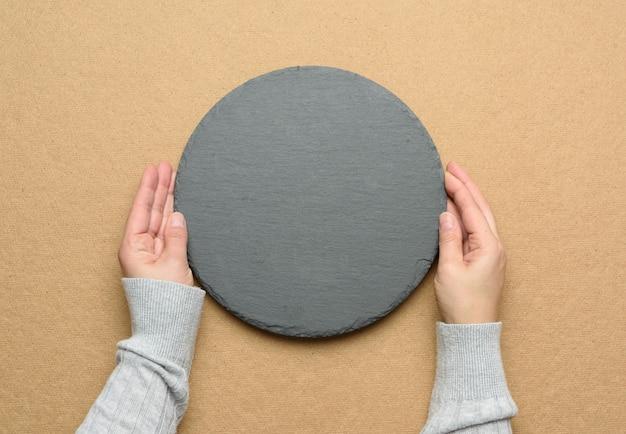 Ręka trzymać pustą okrągłą tablicę łupkową kuchenną na brązowym tle, widok z góry