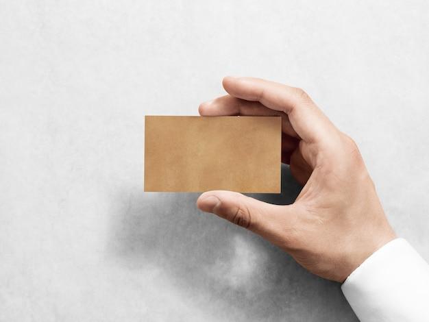 Ręka trzymać pusty projekt wizytówki zwykły kraft