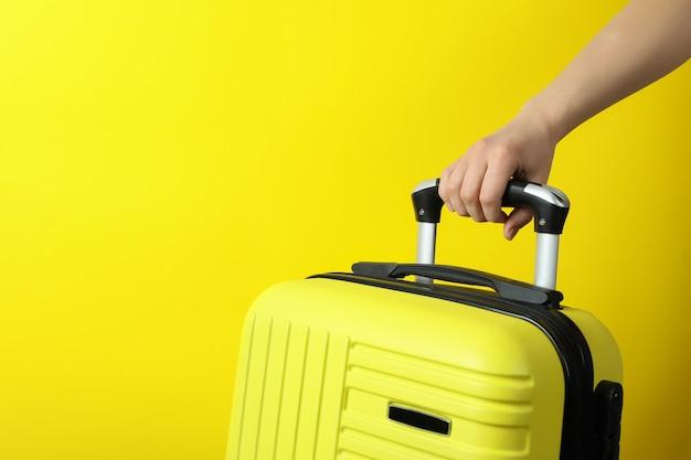 Ręka trzymać torbę podróżną na żółtym tle