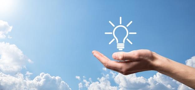 Ręka Trzymać żarówkę. Trzyma W Dłoni świecącą Ikonę Pomysłu. Z Miejscem Na Tekst. Koncepcja Pomysłu Na Biznes. Koncepcje Innowacji, Burzy Mózgów, Inspiracji I Rozwiązań. Premium Zdjęcia