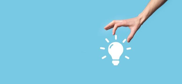Ręka trzymać żarówkę. trzyma w dłoni świecącą ikonę pomysłu. z miejscem na tekst. koncepcja pomysłu na biznes. koncepcje innowacji, burzy mózgów, inspiracji i rozwiązań.