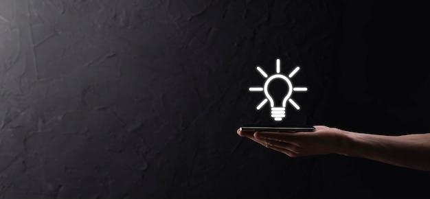 Ręka trzymać żarówkę. trzyma w dłoni świecącą ikonę pomysłu. z miejscem na tekst.koncepcja
