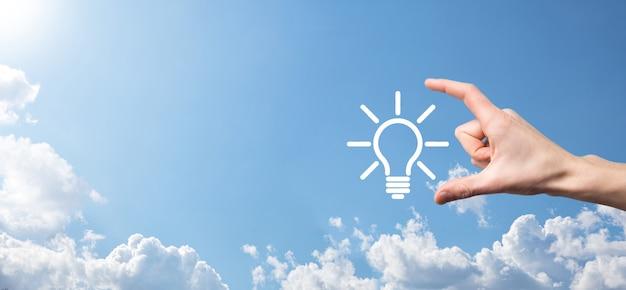 Ręka trzymać żarówkę. w dłoni trzyma świecącą ikonę pomysłu. z miejscem na tekst, koncepcja pomysłu na biznes, innowacje, burza mózgów, inspiracje i koncepcje rozwiązań.