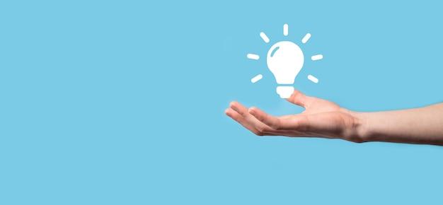 Ręka trzymać żarówkę. w dłoni trzyma świecącą ikonę pomysłu. z miejscem na tekst.