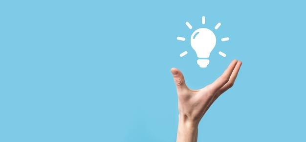 Ręka trzymać żarówkę. w dłoni trzyma świecącą ikonę pomysłu. z miejscem na tekst