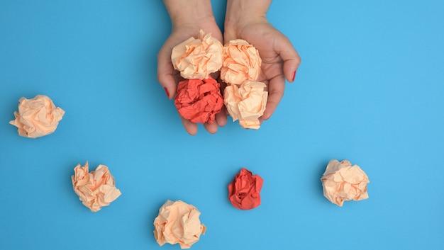 Ręka trzymać zmięte arkusze kolorowego papieru na niebieskim tle. koncepcja rozwiązania, burza mózgów, sprzeciw i konfrontacja, mediator w rozwiązaniu problemu