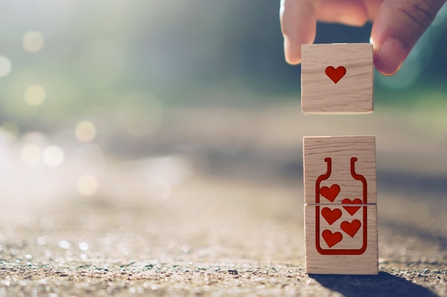 Ręka trzymaj drewniany sześcian z ikoną znak serca i skopiuj światło słoneczne natury przestrzeni, którą możesz umieścić tekst na tle. koncepcja sezon miłości valentine.