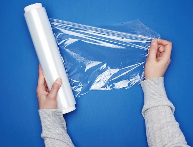 Ręką trzymaj dużą rolkę nawiniętej białej przezroczystej folii do pakowania żywności