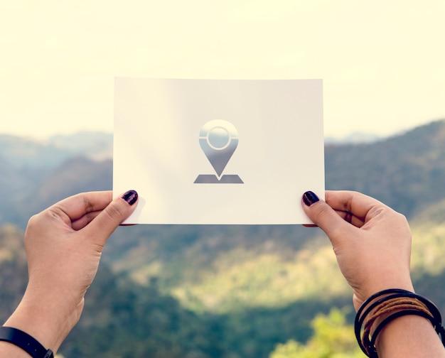 Ręka trzymaj pin tag paper carving z mountain background
