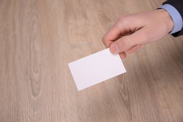 Ręka trzymaj pustą białą makietę karty z zaokrąglonymi narożnikami