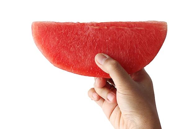 Ręka trzymająca arbuza pokrojonego w trójkątny kształt.