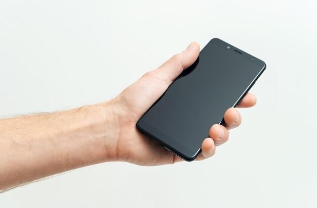 Ręka trzymająca czarny smartfon