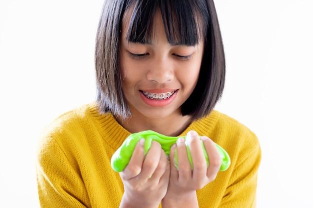 Ręka trzymająca domowej roboty zabawkę zwaną szlamem, dzieci bawiące się i kreatywne dzięki eksperymentowi naukowemu