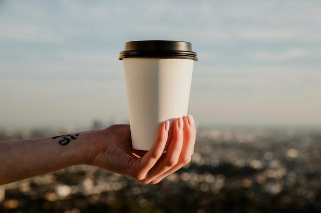 Ręka trzymająca filiżankę kawy na wynos z makieta z widokiem na miasto