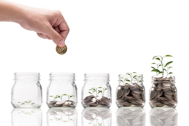 Ręka trzymająca i wkładająca monetę do oszczędzania szklanego słoika ze świecącą rośliną i wzrostem monet.