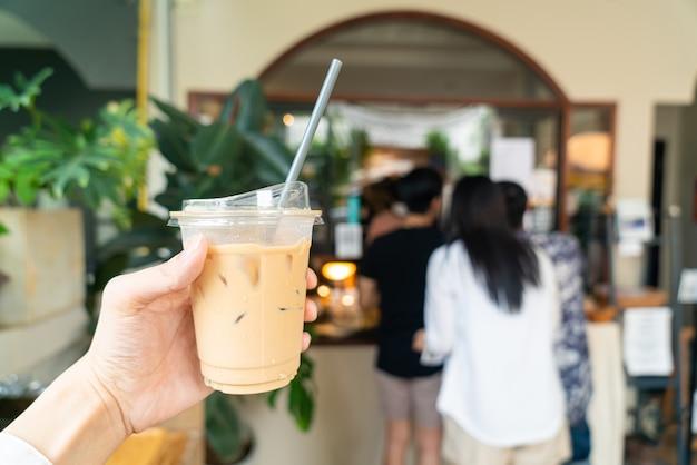 Ręka trzymająca kawę latte w szklance na wynos