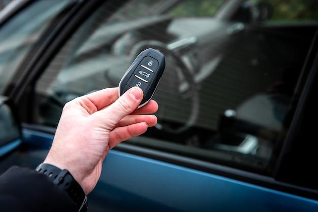 Ręka trzymająca kluczyk samochodowy z pilotem i naciskając przycisk