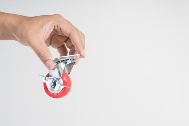 Ręka trzymająca kółka metalowe z miękką plastikową oponą do mebli