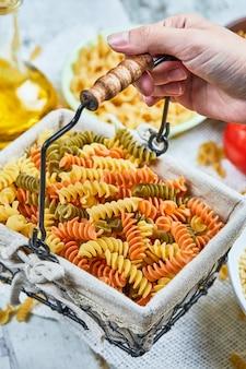 Ręka trzymająca kosz surowego makaronu fusilli z różnymi makaronami i warzywami na marmurowym stole.