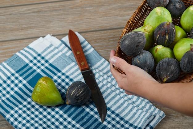 Ręka trzymająca kosz z figami na drewnianym stole z nożem i obrusem.