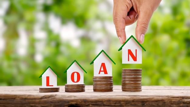 Ręka trzymająca model domu z tekstem pożyczki i małym modelem domu na stosie monet