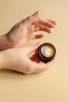 Ręka trzymająca niemarkowy słoik z ciemnego szkła z kremem nawilżającym do twarzy