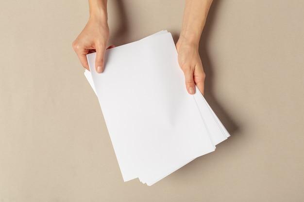 Ręka trzymająca papiery w rozmiarze a4