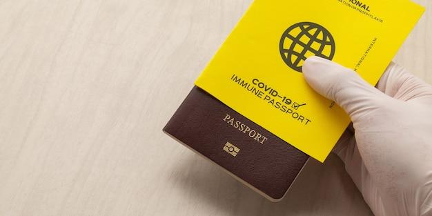Ręka trzymająca paszporty szczepionki jako dowód, że posiadacz został zaszczepiony przeciwko covid-19, wymóg dotyczący podróży międzynarodowych. tło transparent.