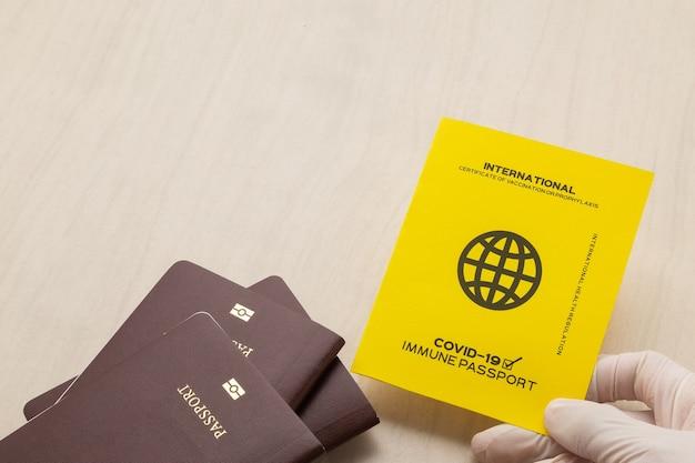 Ręka trzymająca paszporty szczepionki jako dowód, że posiadacz został zaszczepiony przeciwko covid-19, wymóg dotyczący podróży międzynarodowych.